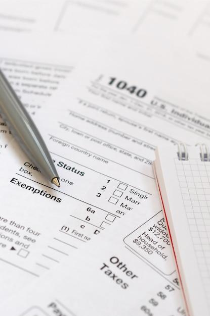 Le stylo et le cahier se trouvent sur le formulaire fiscal us individual Photo Premium