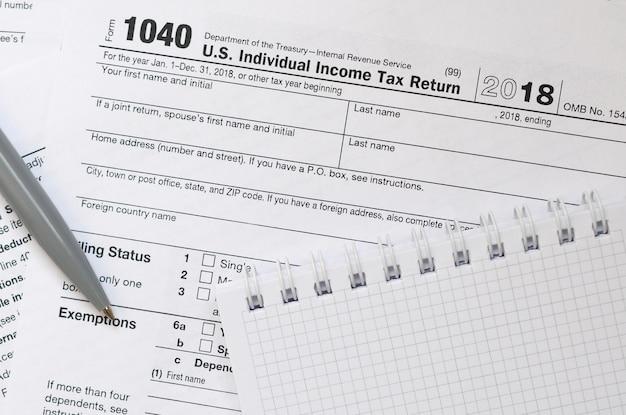 Le stylo et le cahier se trouvent sur le formulaire d'impôt 1040 us déclaration de revenus des particuliers Photo Premium
