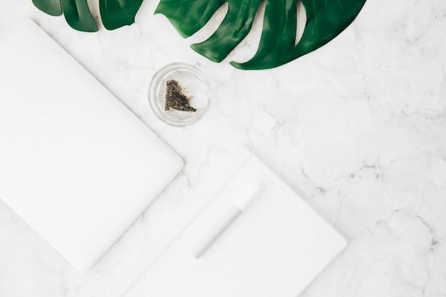 Stylo; journal intime; tablette numérique; feuille de monstera et sachet de thé dans le verre sur fond texturé en marbre Photo gratuit