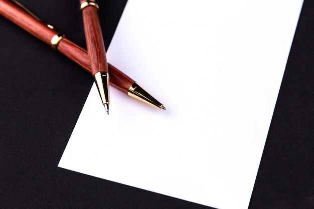 Stylo de luxe et porte-mine en bois et or avec une feuille de papier blanche Photo Premium