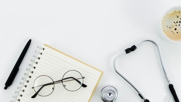 Stylo noir; lunettes sur le bloc-notes en spirale; stéthoscope et tasse à café sur fond blanc Photo gratuit