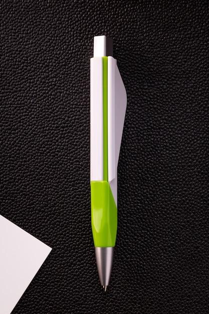 Stylo vert et carte blanche sur fond sombre. stylo à bille vierge pour votre conception. Photo Premium