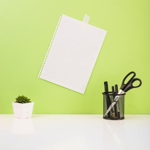 Stylos et ciseaux dans le support près du papier coincé sur le mur vert Photo gratuit