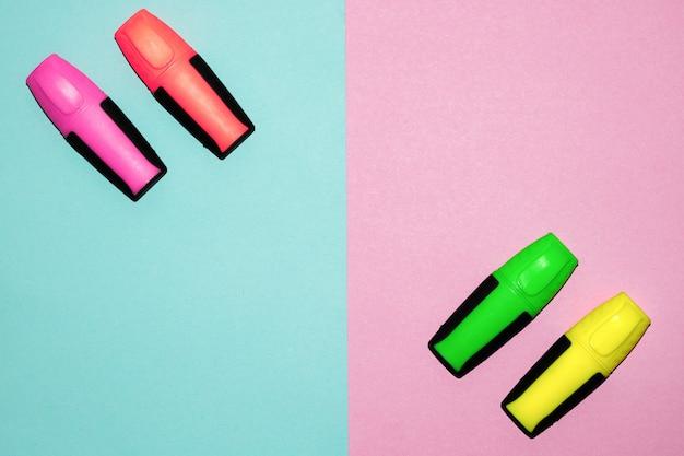 Stylos feutre multicolores sur fond rose et bleu pastel. marqueurs colorés Photo Premium