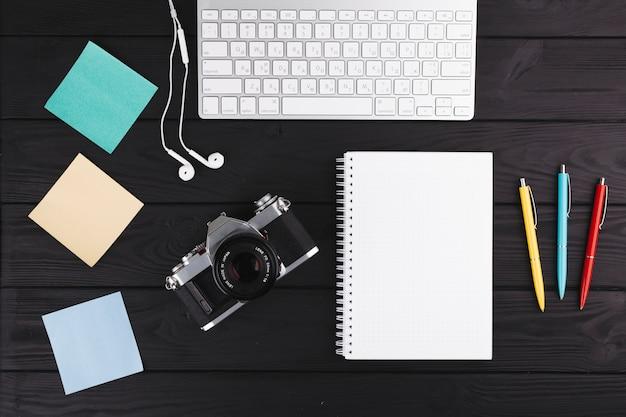 Stylos près de cahier, appareil photo, écouteurs, papiers et clavier Photo gratuit