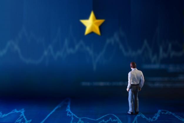 Succès En Affaires Ou Concept De Talent. Un Homme D'affaires Miniature Se Tenant Sur Le Graphique Financier Et Regardant Sur Le Mur Avec L'étoile Dorée Jaune Photo Premium