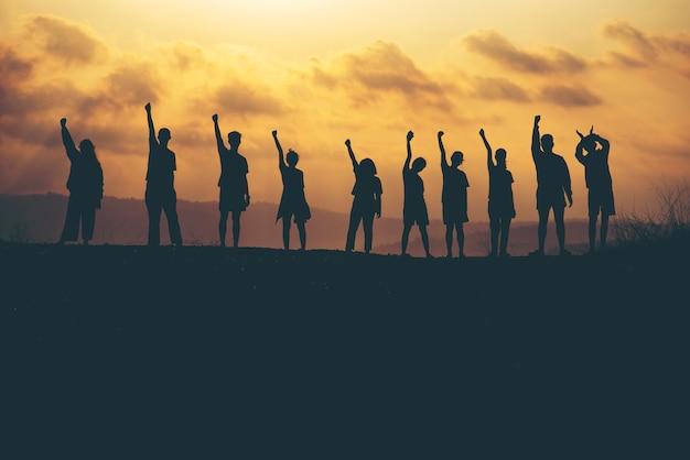 Succès de la collaboration au travail d'équipe et de la liberté sur fond de coucher de soleil silhouette. concept d'entreprise Photo Premium