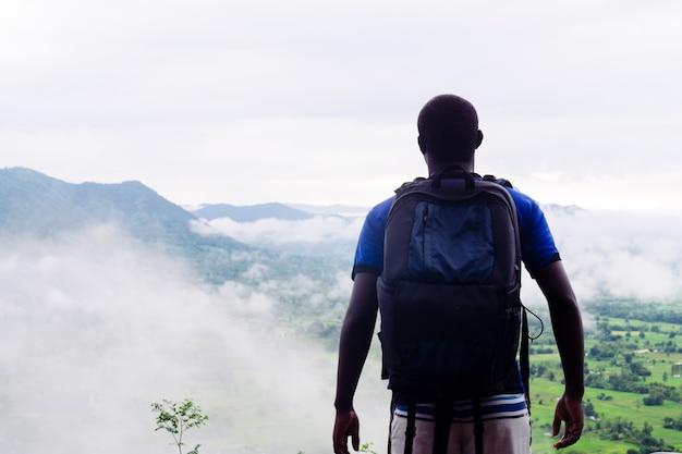 Succès grimpeurs africains regardant au sommet de la colline couverte de brouillard et de pluie. Photo Premium