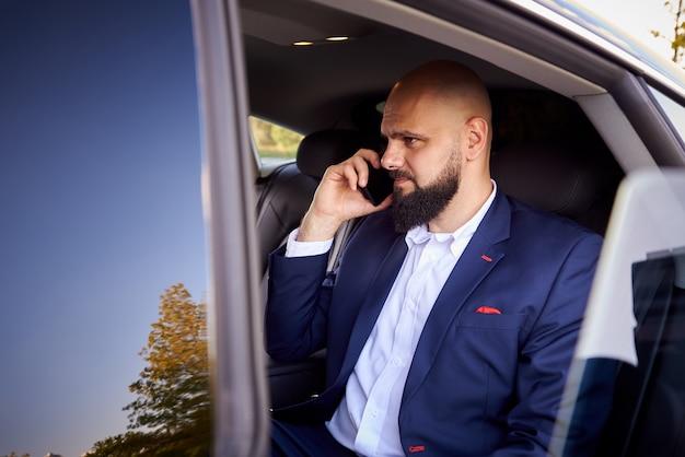 Succès jeune homme parlant au téléphone dans une voiture. Photo Premium