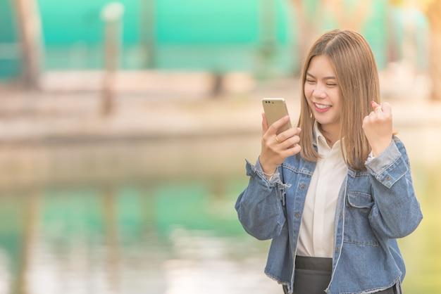 Succès Et Surpris Jeune Femme Asiatique En Utilisant Un Téléphone Intelligent à L'extérieur Photo Premium