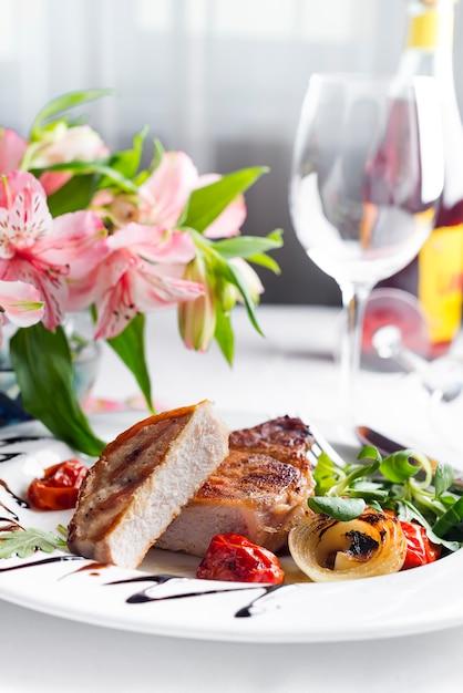 Succulentes portions juteuses et épaisses de steaks grillés servis avec tomates et légumes rôtis Photo Premium