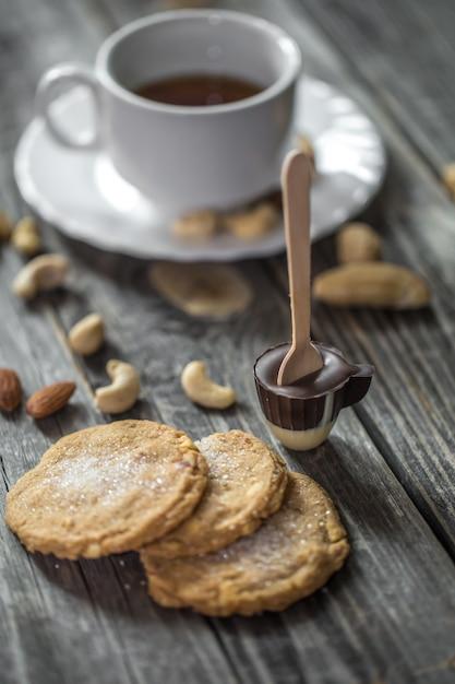 Sucette Au Chocolat En Forme De Petite Tasse Avec Une Tasse De Thé Et De Noix Sur Bois Photo gratuit