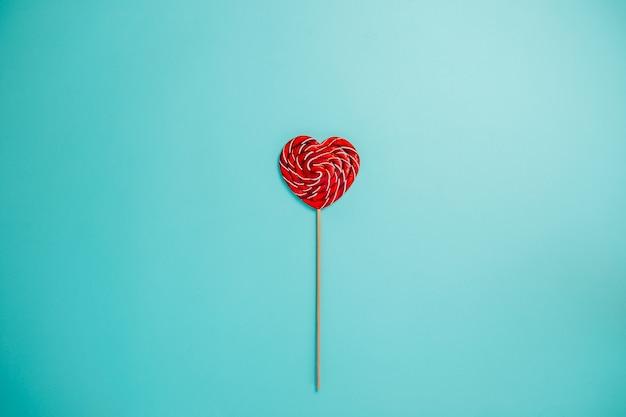 Sucette Rouge En Forme De Coeur Avec Long Bâton. Une Sucette Au Milieu. Photo Premium