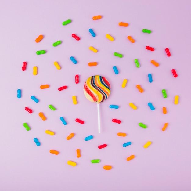 Sucette de sucre entouré de bonbons colorés de marmelade sur fond rose Photo gratuit