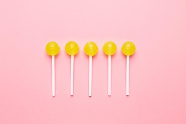 Sucette sucrée jaune bonbon rose pastel. composition minimaliste. Photo Premium