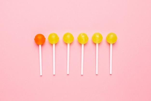 Sucette sucrée jaune et orange sur rose pastel. composition minimaliste. Photo Premium