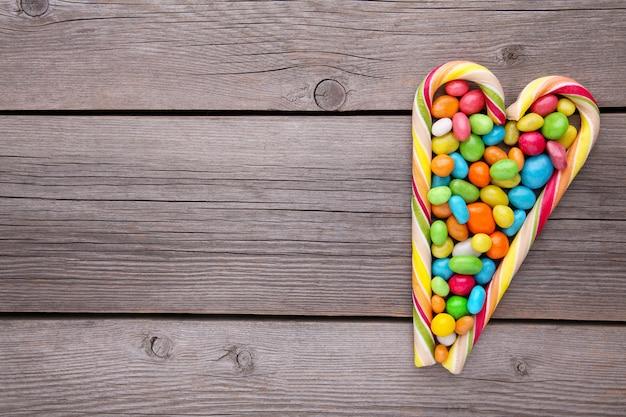 Sucettes colorées et bonbons ronds de couleurs différentes sur fond gris Photo Premium