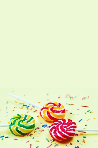 Sucettes Colorées Et Confettis Sur Fond Jaune. Bonbons Pour La Fête. Sucre Photo Premium