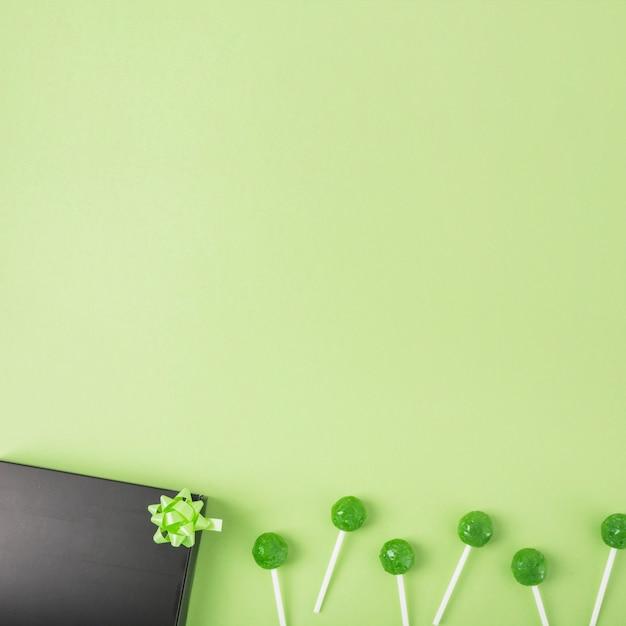 Sucettes vertes avec boîte-cadeau noire et archet sur fond vert Photo gratuit