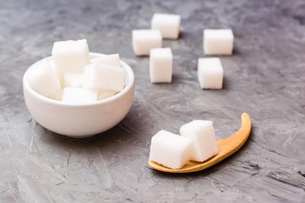 Sucre cubes dans un bol blanc et une cuillère en bois sur une table Photo Premium