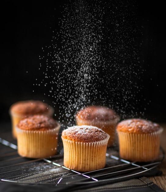 Sucre en poudre versé sur muffin Photo gratuit