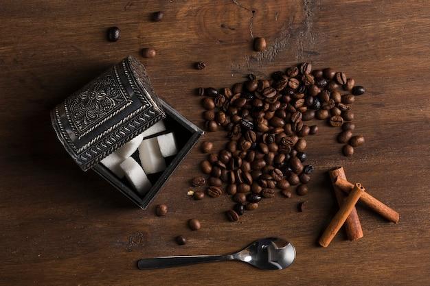 Sucrier et grains de café près des bâtons de cannelle et de la cuillère Photo gratuit