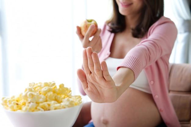 Suivre un régime femme enceinte refusant le pop-corn et choisissant une pomme rouge. Photo Premium