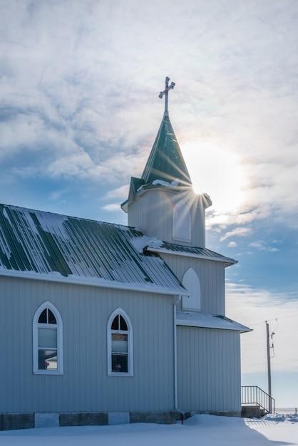 Sunburst au-dessus de l'église historique luthérienne de la paix dans les prairies en saskatchewan, canada Photo Premium
