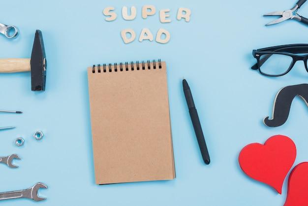 Super papa inscription avec bloc-notes et outils Photo gratuit