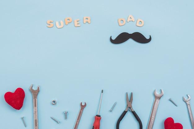 Super papa inscription avec outils et moustache en papier Photo gratuit