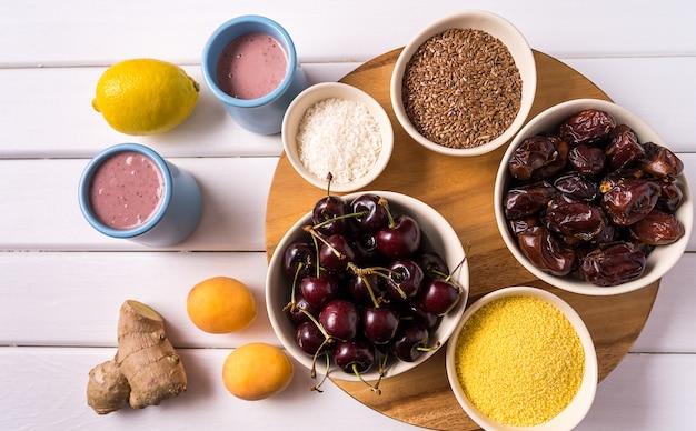 Superaliments dans des bols, fruits frais, smoothie au gingembre et baies sur une table en bois blanche. Photo Premium