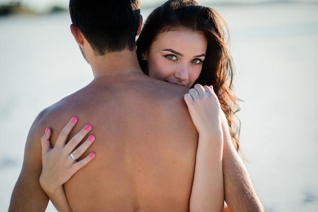 Superbe brune embrasse un homme nu et tient ses mains sur son dos Photo gratuit