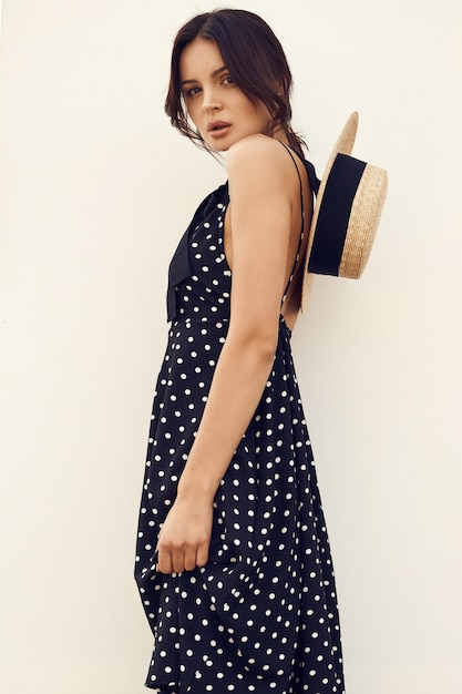 Superbe brune en robe fashion avec chapeau posant contre un mur blanc Photo Premium
