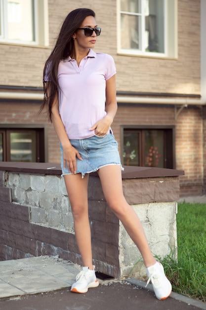 Une Superbe Brune Vêtue D'un T-shirt Et D'une Jupe En Jean Se Redresse Les Cheveux Dans Une Rue De La Ville. Photo Premium