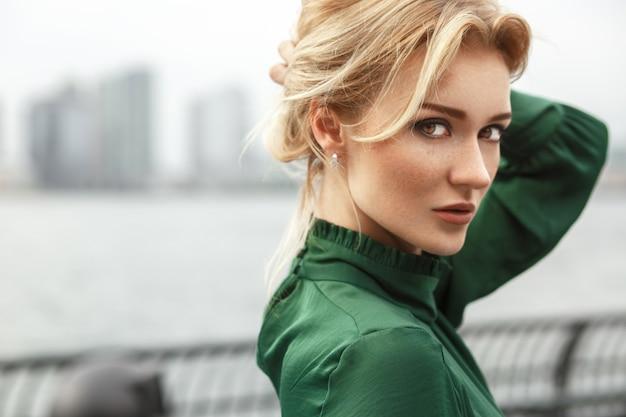 Superbe dame en robe verte pose devant une rivière à new york Photo gratuit