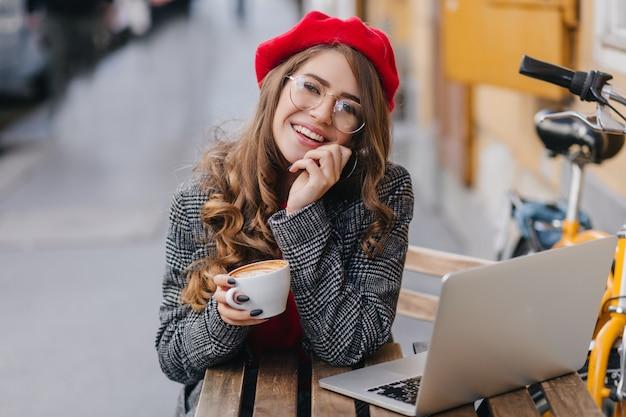 Superbe étudiante Travaillant Avec Un Ordinateur Portable Dans Un Café En Plein Air Dans Un Froid Matin D'automne Photo gratuit