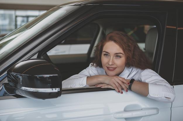 Superbe femme achète une voiture neuve chez le concessionnaire Photo Premium