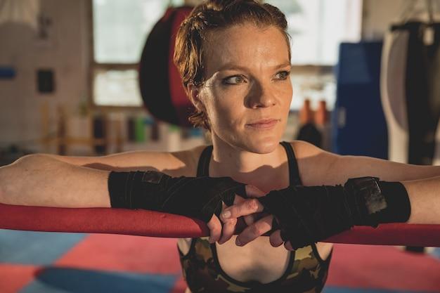 Superbe Femme, Combattant Mma Dans La Salle De Gym Pendant L'entraînement. Se Préparer Pour Un Match En Cage Dure Photo Premium