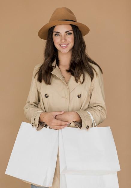 Superbe femme en manteau et chapeau avec des filets à provisions à deux mains Photo gratuit