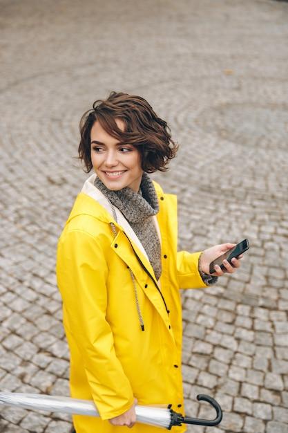 Superbe Femme Marchant Sur Des Pavés Dans Le Centre-ville Avec Téléphone Portable Et Parapluie Dans Les Mains à La Recherche D'un Ami Photo gratuit