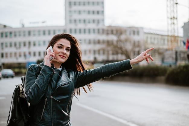 Superbe femme parlant dans la rue, prenant un taxi. Photo Premium