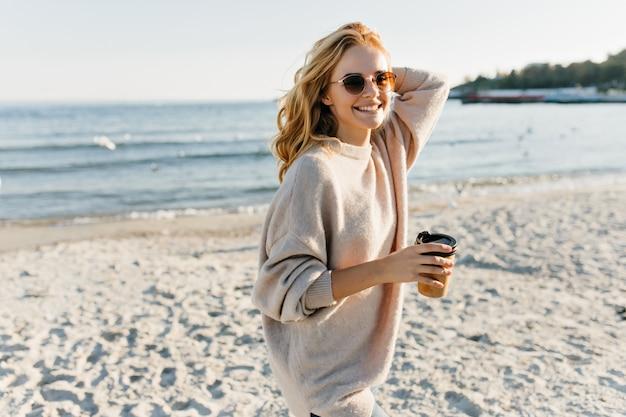 Superbe Femme En Pull Debout Sur La Côte De La Mer. Femme Blonde Fashiinable Appréciant Le Thé Près De L'océan. Photo gratuit