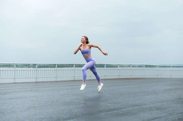 Superbe femme qui court le long du lac Photo gratuit