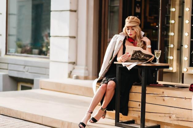 Superbe Femme En Robe Noire Reposant Dans Un Café En Plein Air Et Lisant Le Journal. Fille élégante En Manteau Marron Et Chapeau Assis à La Table Avec Verre De Champagne Et Ami En Attente. Photo gratuit