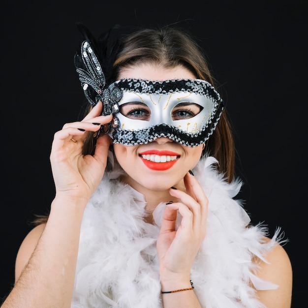 Superbe femme souriante avec des plumes de boa blanc sur fond noir Photo gratuit