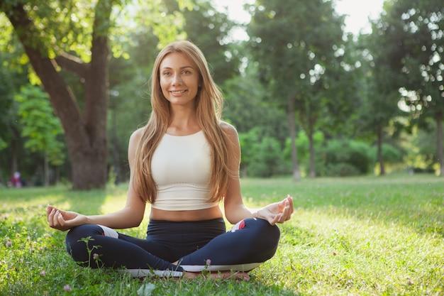 Superbe femme sportive faisant du yoga au parc Photo Premium