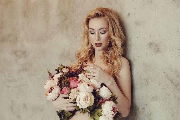 Superbe Femme Tenant Un Bouquet De Roses Photo gratuit