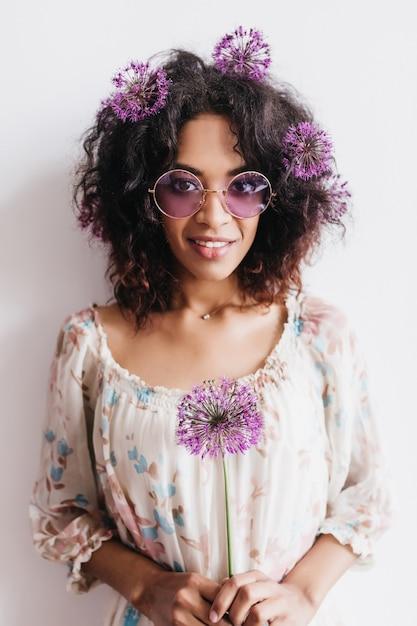 Superbe Fille Africaine à Lunettes De Soleil Posant Avec Allium. Plan Intérieur D'un Adorable Modèle Féminin Bouclé Avec Des Fleurs Violettes. Photo gratuit