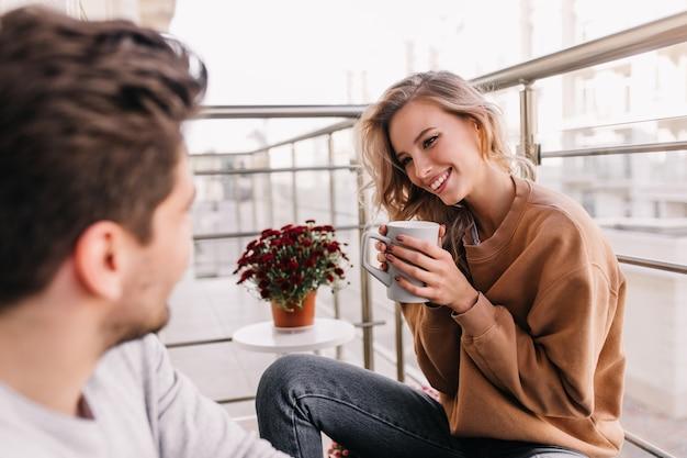 Superbe Fille Avec Une Coiffure Frisée, Boire Du Café Au Balcon. Portrait De Dame Heureuse Se Détendre Avec Son Mari. Photo gratuit