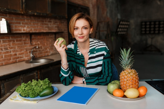 Superbe jeune femme en bonne santé mange des pommes dans sa cuisine loft moderne. prof de fitness. Photo gratuit